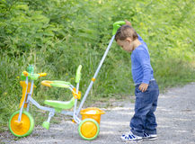 Boy with tricycle. Little boy playing with tricycle in park Stock Photo