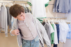 The boy tries on clothes in store. The boy tries on clothes in the childrens clothing store royalty free stock photos