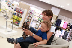 Boy tries on footwear. With mothers assistance in a store royalty free stock photos
