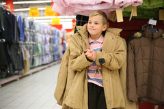 Boy tries on  jacket in shop. Boy tries on big adult jacket in shop Stock Photography