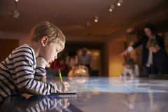 Boy On Trip To Museum Looking At Map And Writing In Notebook Royalty Free Stock Images