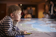 Boy On Trip To Museum Looking At Map And Writing In Notebook Stock Photo
