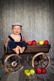 Boy in a trolley, full of apples Stock Photos