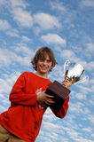 Boy with trophy. A happy boy holding up a big trophy (sky background Royalty Free Stock Images