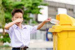 Boy trow the garbage. Young Thai student boy in school uniform trow the garbage in the yellow bin and he show bad smelling stock image