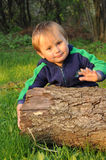 Boy with trunk. Young boy moving a piece of a wooden trunk in the garden Royalty Free Stock Photos