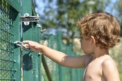 A boy try to escaping. A boy who tries to sneak out through the gate Royalty Free Stock Photography