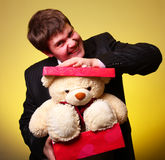 Boy try to hide teddy bear in present box Stock Image