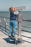 Boy try to looks in binocular on the sea pier Stock Photography