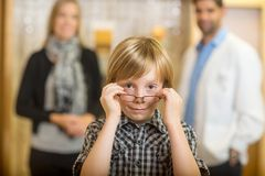 Boy Trying Eyeglasses With Optometrist And Mother. Portrait of boy trying eyeglasses with optometrist and mother standing in background at store Royalty Free Stock Photos