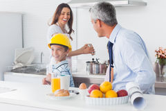 Boy trying on fathers hard hat with parents laughing Stock Photo
