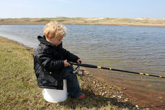 Boy is trying to catch some fish. Boy is fishing in a small lake stock photos
