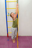 The boy is trying to climb a rope Stock Image