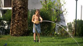 Boy trying to cope with water jet when watering lawn. Boy struggling with water jet when watering the lawn in the garden near the house on hot summer day stock video