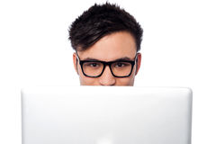 Boy trying to hide his face behind laptop Royalty Free Stock Photography