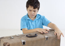 Boy trying to open a suitcase stock images