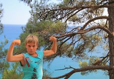 Boy is trying to show his muscules Stock Photo