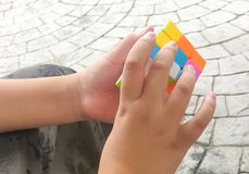 A boy trying to solving the 3 by 3 rubic cube royalty free stock photos