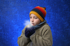 Boy trying to warm his hands Royalty Free Stock Photography