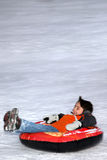 Boy Tubing Down Snowy Hill. Royalty Free Stock Photos