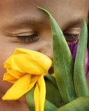 Boy and Tulips. Close up of a little boy with purple and yellow tulips Stock Photo