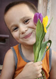 Boy and Tulips. Close up of a little boy with purple and yellow tulips Stock Images