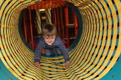Boy in tunnel on playground Stock Images