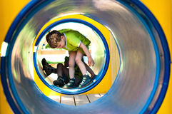 Boy in the tunnel. The boy in the tunnel at the playground. The tunnel is blue. Boy's t-shirt light green color. He is wearing orthopedic shoes Stock Photography