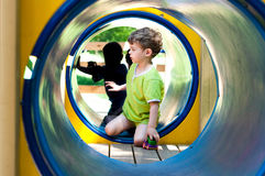 Boy in the tunnel. The boy in the tunnel at the playground. He reaches for toy car with one hand.  The tunnel is blue. Boy's t-shirt  light green color Stock Images