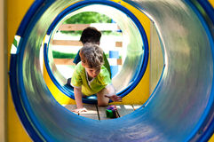 Boy in the tunnel. The boy in the tunnel at the playground. He reaches for toy car. The boy sat on his knees and leans on one arm. The tunnel is blue. Boy's t Royalty Free Stock Image
