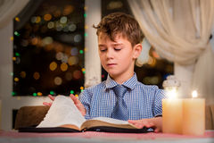 Boy turning page of book. Child and book by candlelight. He read half of it. Huge collection of poems Royalty Free Stock Images