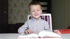 Boy turning the pages of big book. As if reading then smiling at the camera and sneezing stock video footage