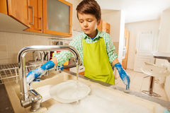 Boy turning on the tap and rinsing dishes in sink Stock Photo