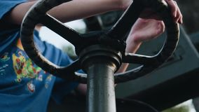 The boy turns the metal steering wheel control. Close-up of the child`s hands. Development of children stock video footage