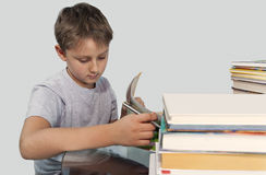 Boy turns the textbook surrounded by books Stock Photography