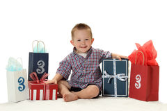 A Boy Turns Three Years Old. A 3 year old boy sits with his presents royalty free stock photography