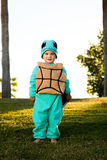 Boy In Turtle Costume. A boy dressed as a turtle for Halloween stands on a sloping hill in a park Royalty Free Stock Images