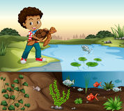 Boy and turtle by the pond Royalty Free Stock Images