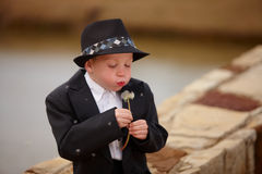 Boy in tuxedo blowing dandielion Royalty Free Stock Photography