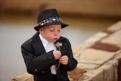 Boy in tuxedo blowing dandielion. Boy blowing dandielion in tuxedo and hat Royalty Free Stock Photography