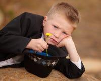 Boy in tuxedo sad with yellow flower. Boy in tuxedo and hat with sad face and yellow flower Stock Photos