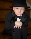 Boy in tuxedo and top hat sitting. Little boy dressed up in top hat and tuxedo Stock Photos