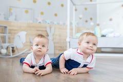 Boy twins playing on the floor. Funny  boy twins playing on the floor in the nursery Stock Photos