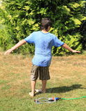 Boy twisting behind sprinkler. Barefoot little boy - kid in blue t-shirt and brown shorts twisting behind splashing sprinkler and soaking wet royalty free stock photos