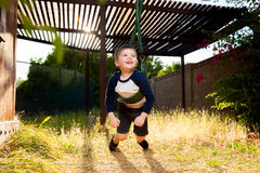 Boy Twists A Swings Chains To Spin. A young boy lays on his belly on a swing and twists it up so that he can spin. He looks excited royalty free stock photos