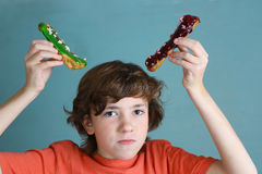 Boy with two eclairs acting funny horn Stock Images
