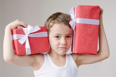 Boy with two gifts show muscle. Boy with two boxes of gifts on his shoulders Stock Photography