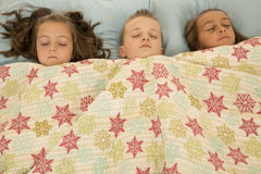 Boy and two girls asleep under a blanket Stock Photography