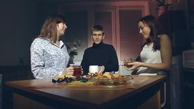 The boy and two girls are drinking tea. The young man and two young girls sitting in the evening in the kitchen and drink tea stock video