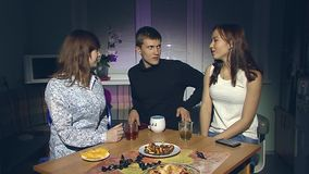 The boy and two girls are drinking tea. The young man and two young girls sitting in the evening in the kitchen and drink tea stock video footage